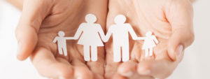 A pair of hands holding a family of paper cut out people.