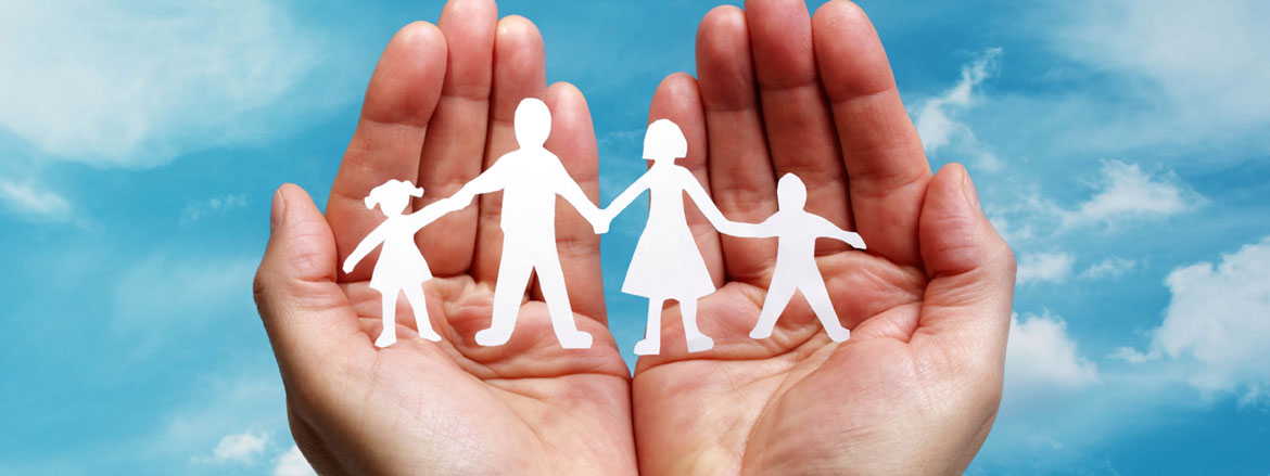 A photograph of a pair of hands holding a paper cut out family, against a cloudy sky background.